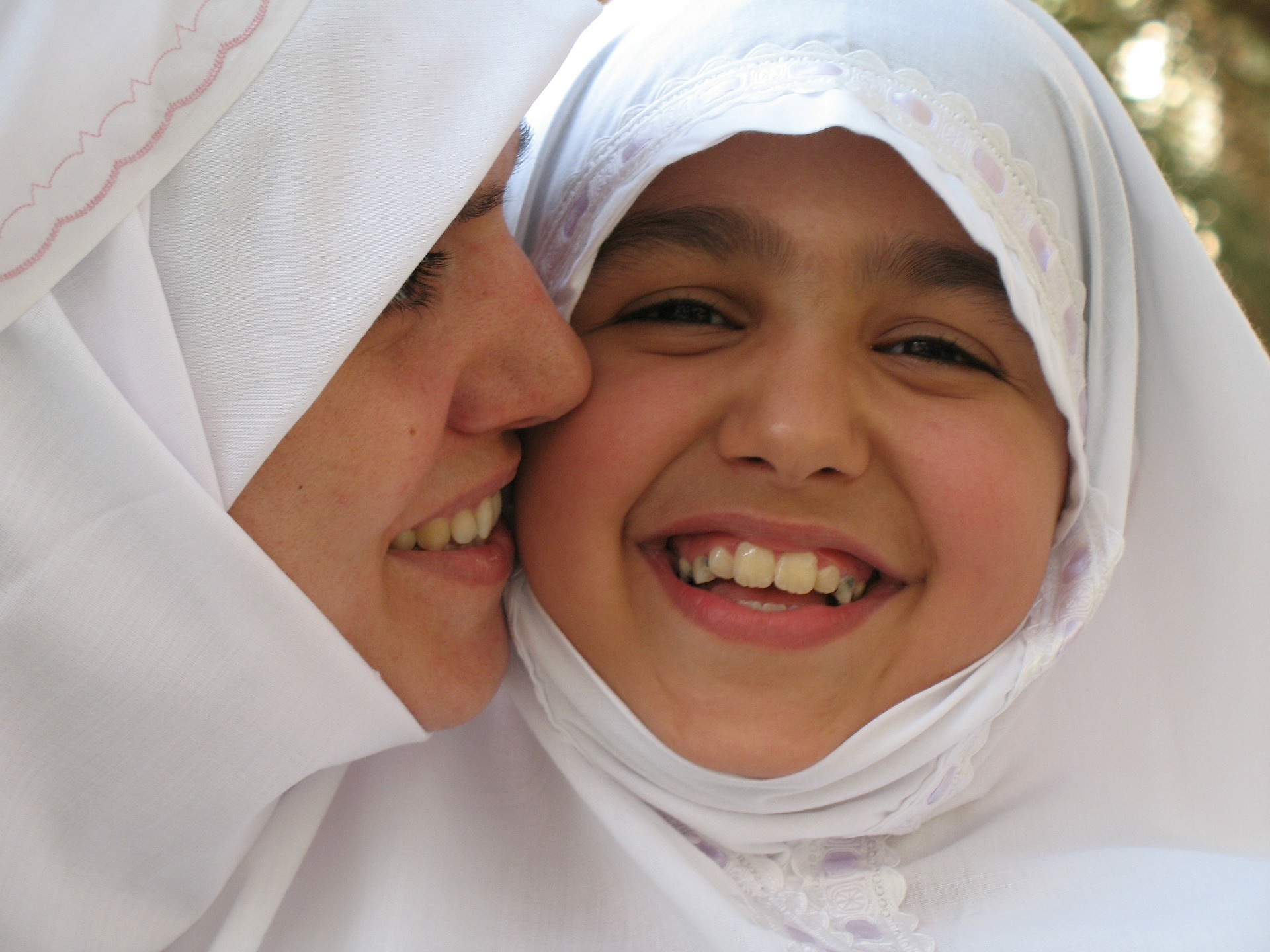 two smiling girls in burkas