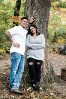 Emily and Sam Papa leaning against a large tree posing for fall photos