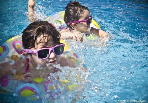 Kids swimming in pool wearing sunglasses