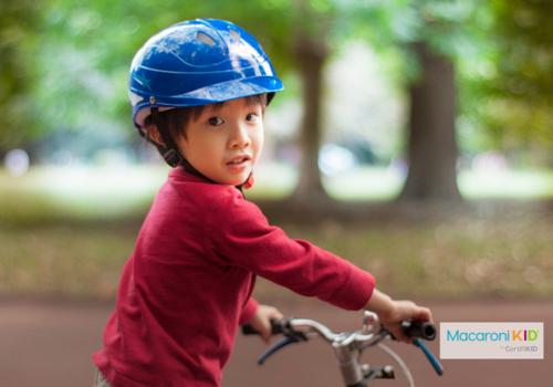 Little Boy is wearing a bashful smile on bike.