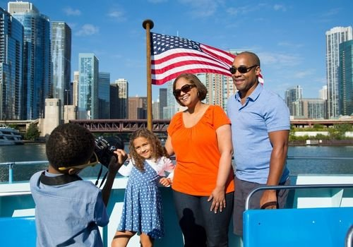Family poses for photo with Chicago skyline in background - aboard Mercury Cruises