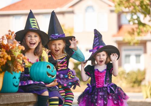 Kids in halloween costumes with teal pumpkins