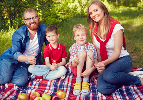 Family of four sitting on a blanket holding sparklers