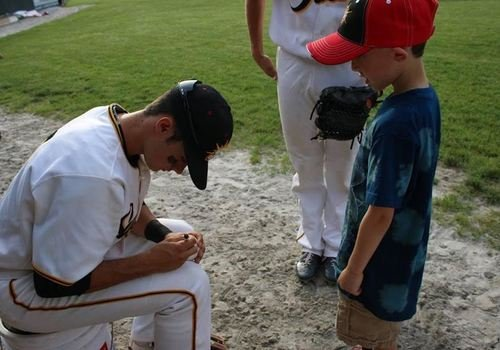 baseball player signs autograph for child