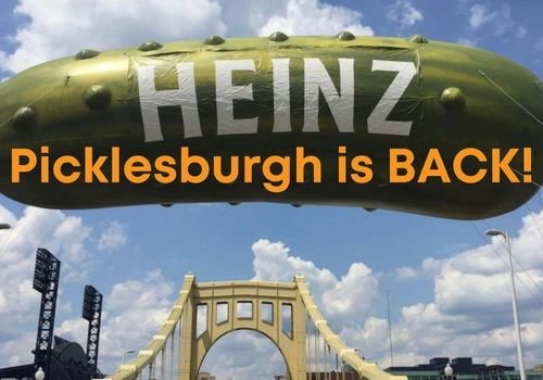 Giant green, inflatable Heinz pickle over a yellow Pittsburgh bridge with the words Picklesburgh is BACK! in orange as an overlay
