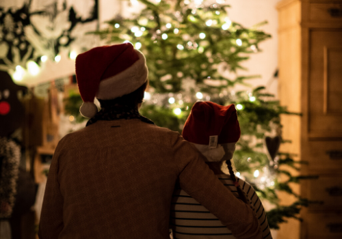 child and parent in front of Christmas tree
