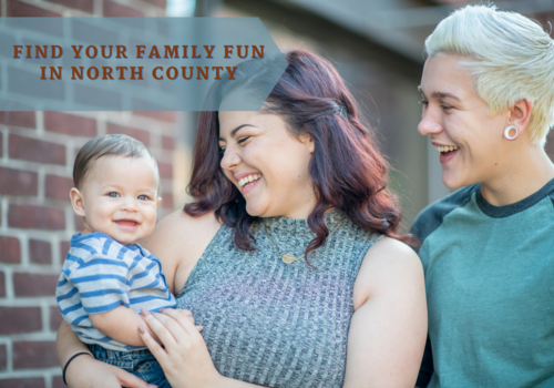 LGBTQ Parents smile as they hold their smiling baby