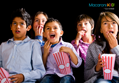 Kids watching a scary movie with bowls of popcorn. Some are laughing and some look scared.