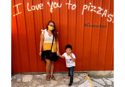 Brittany and son stand in front a red wall at Fire Street Pizza that says I love you to pizzas.