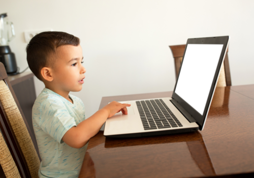 Young boy navigating a touch pad of a laptop