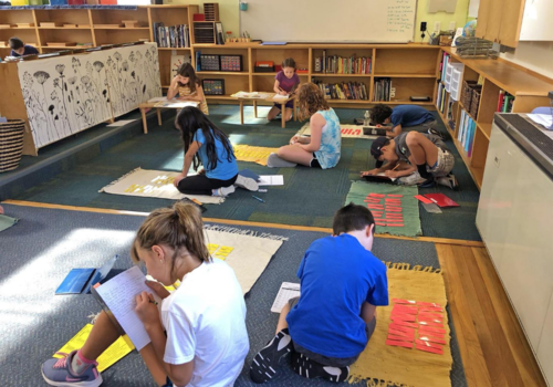 The Montessori classroom naturally provides the space for these Upper Elementary students to spread out to do their work.