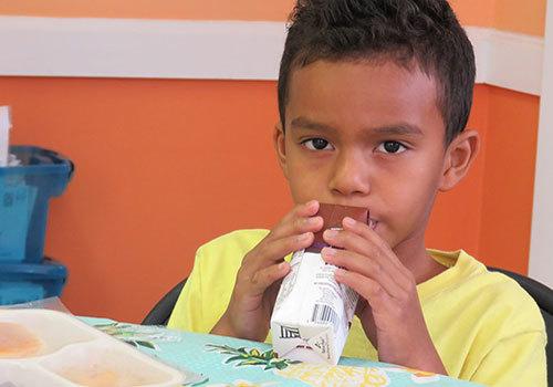 Child enjoying meal during Treasure Coast Food Bank's 2018 Summer Meals program