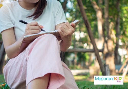 woman writing under tree