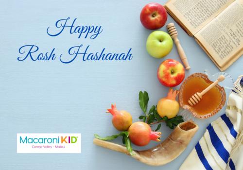 Happy Rosh Hashanah on a light blue background with apples pomegranates, honey, tallit, shofar and prayer book