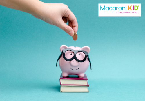 Savings Deals from Macaroni KID Conejo Valley Malibu and CertifiKID photo of a tiny pink piggy bank and with glasses sitting on books and someone adding a penny