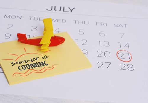 Close up of a July calendar with the date Saturday 21st circled in red. There are yellow Post-it notes that say summer is coming stacked on the calendar with a red and yellow airplane paperweight.