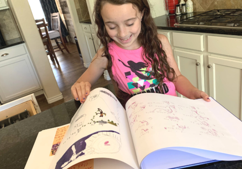 Artimus Art: child looking through her Artimus Art book filled with her personal artwork