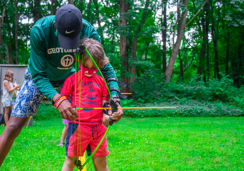 Counselor teaching archery to boy