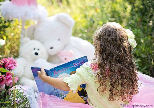 Little Girl reading to her bears