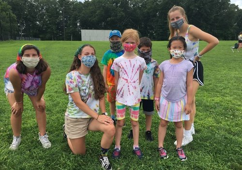 Children in field outdoors with face masks
