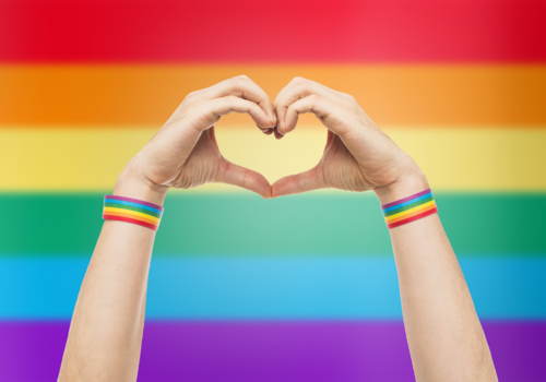 hands in a heart in front of a pride flag