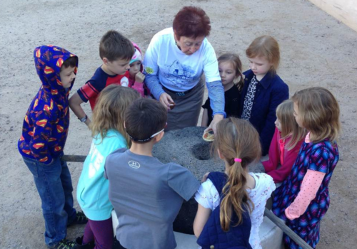 Children gathered around an historic cooking tool