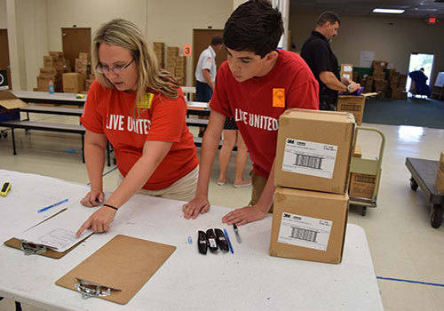 Volunteers Leslie Judd and Evan McCarthy sort supplies during last year's Tools for Success program