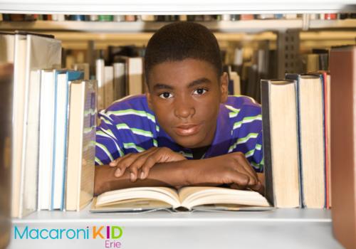 Boy looking through library shelf