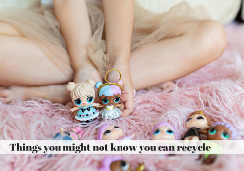 Child holding two LOL Surprise Dolls in hands and six over dolls lay in the carpet around them.