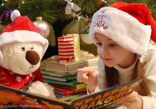 Girl reading to stuffed bear under Christmas tree