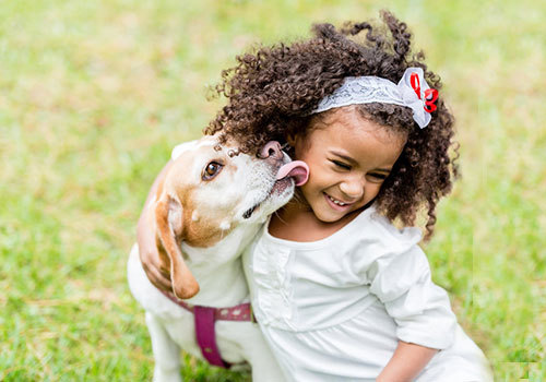 young girl with dog kissing her face