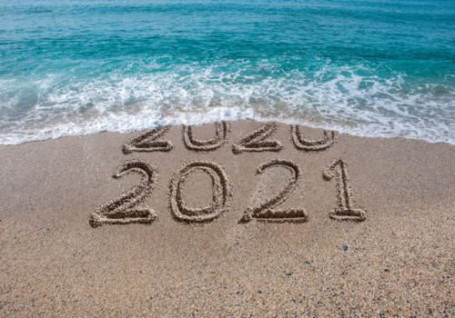 2020 and 2021 written in the sand with a wave washing 2020 away