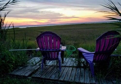 purple beach chairs facing chincoteague VA sunset and bay