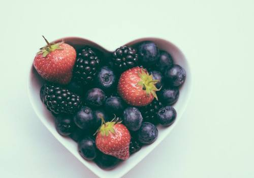 heart shaped bowl filled with blueberries, strawberries and blackberries