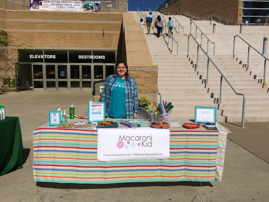 Women behind table with crafts near Gillette Stadium YMCA Healthy Kids
