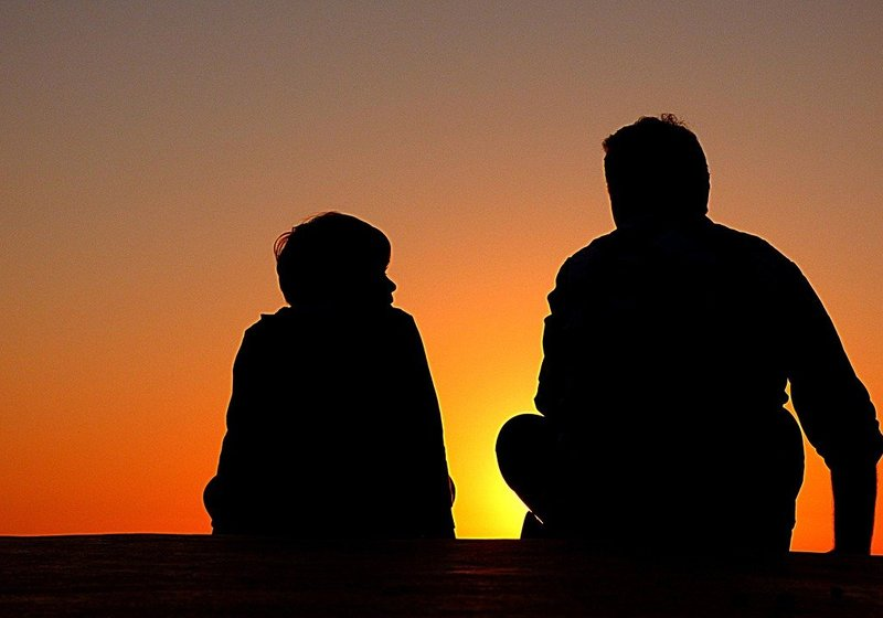 father and son silhouetted against sun
