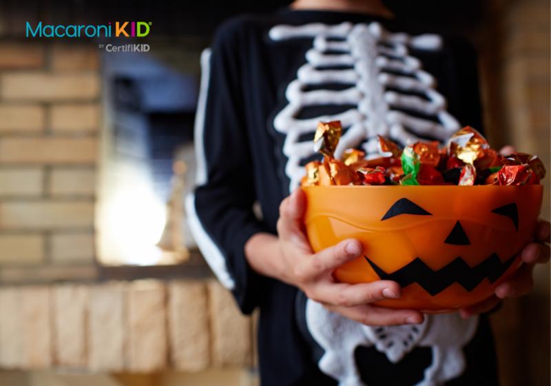 Kid with halloween candy bucket