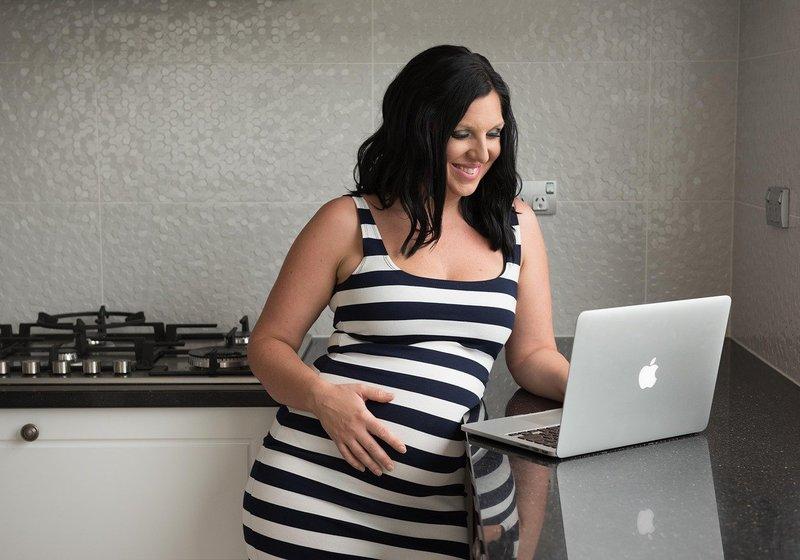 pregnant woman looking at computer