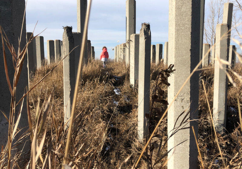 Girl walking between cement piles on a hill