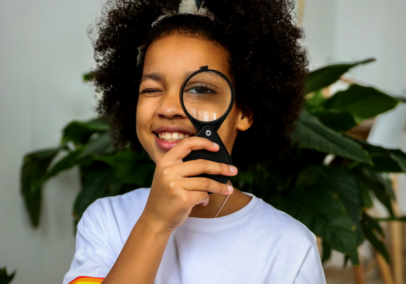 girl with magnifying glass at her eye