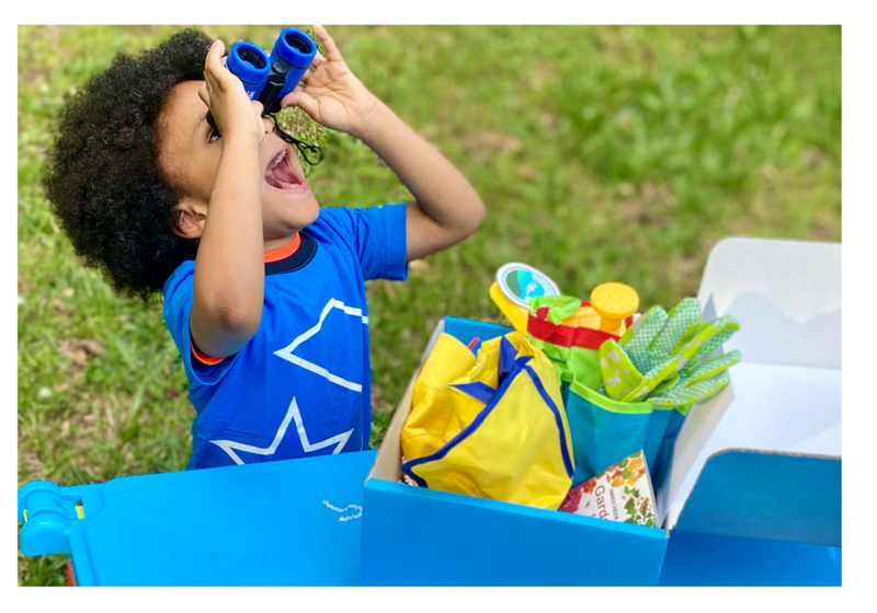 Child playing outside with nature toys, looking up with binoculars