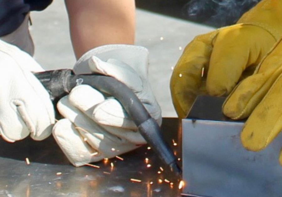 hand holding welding gun with second pair of hands holding metal sheet