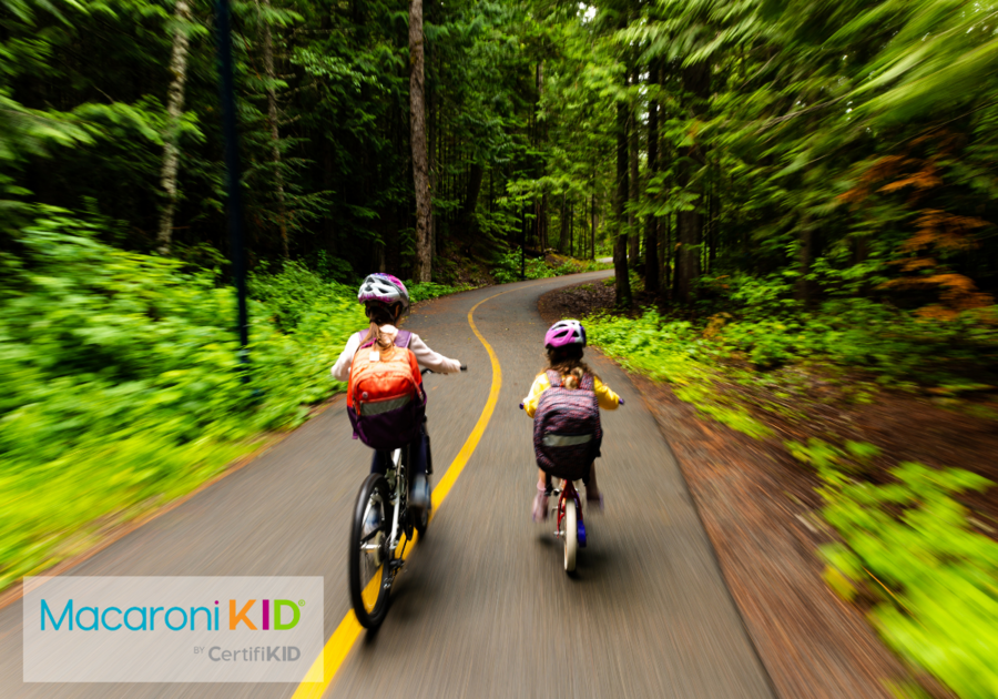 Kids biking to school on a pathway through a lush forest. Bike to school for a sustainable lifestyle. Sisters going to school.