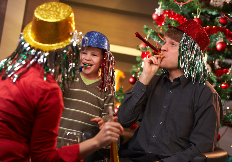 Family with party hats and noise makers. How to celebrate New Year's at home.