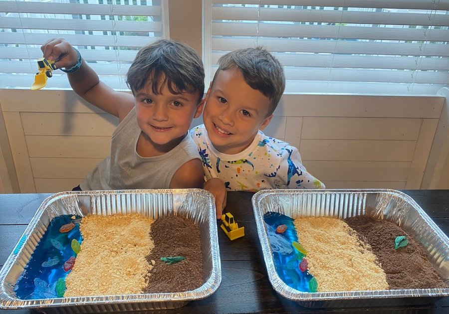 two boys with an edible sensory bin made to look like a beach with Jell-O, crushed cookies