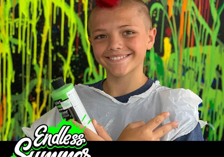 Boy with Red Mohawk standing in front of splash painted wall text in image endless summer youth day camp