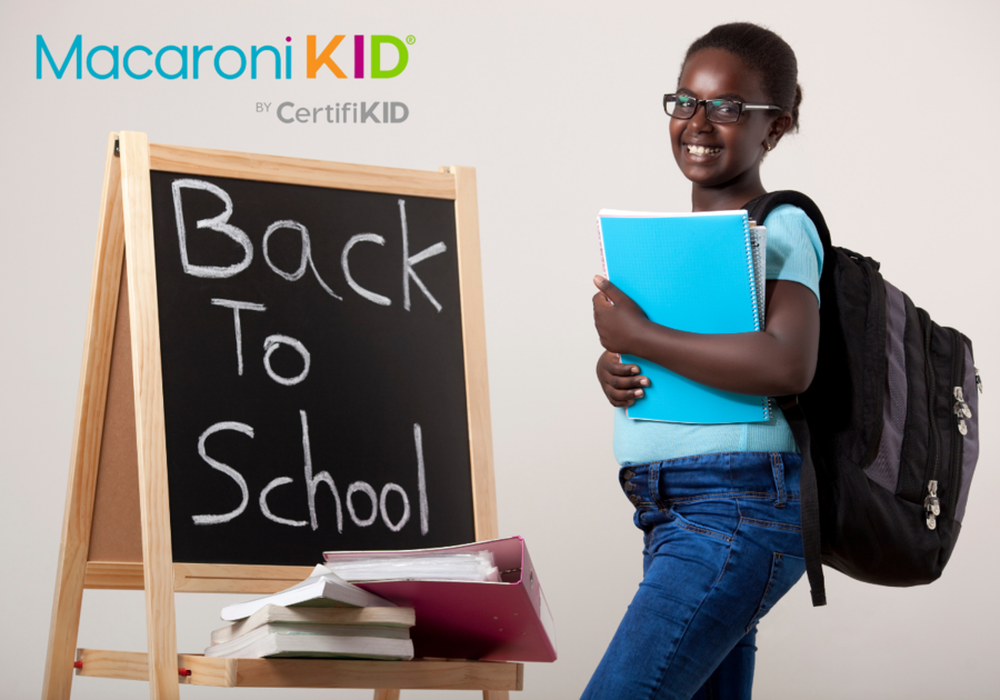 Smiling schoolgirl carrying backpack and holding a notebook in front of back to school sign on chalkboard