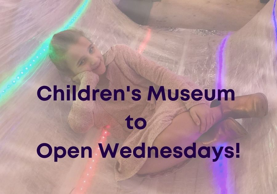 Little girl posing in Tape Scape exhibit with wording stating Children's Museum to open Wednesdays