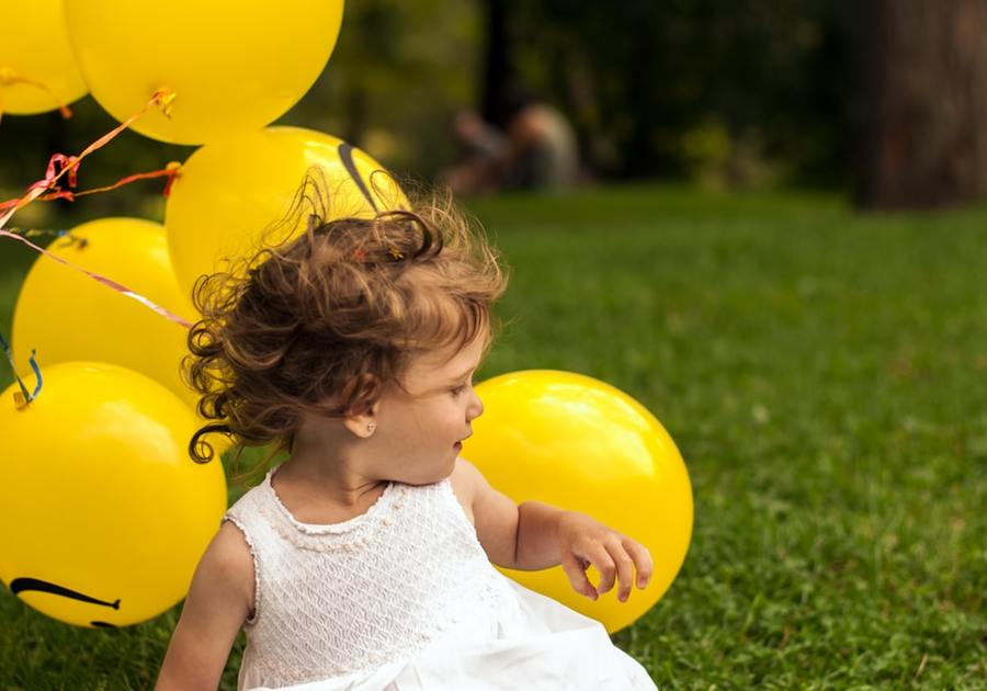 Girl with balloons on grass