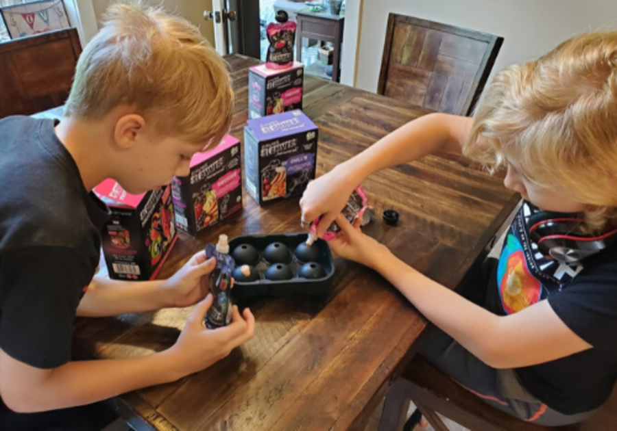 Two kids use organic Slammers Snacks to make popsicles for a fun STEM activity